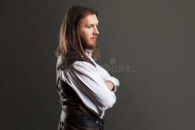 Hübscher männlicher Dampfpunk in einem Retro- Mannporträt der ledernen Weste über grauem Hintergrund lizenzfreie stockfotografie