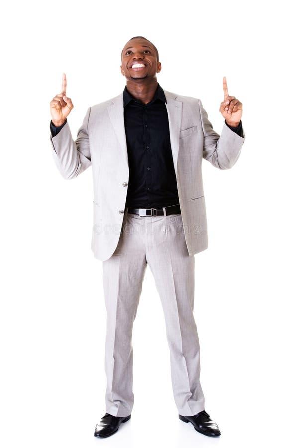 Hübscher männlicher Geschäftsmann, der oben mit den Fingern zeigt. stockbild