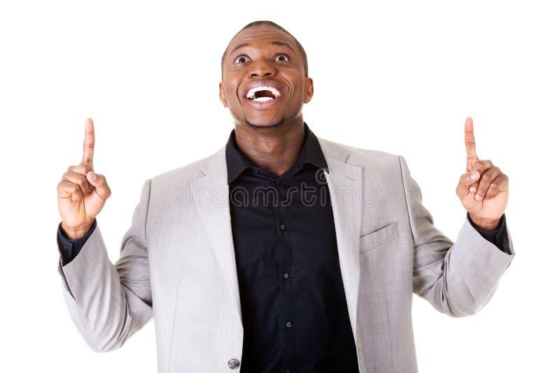Hübscher männlicher Geschäftsmann, der oben mit den Fingern zeigt. lizenzfreies stockfoto