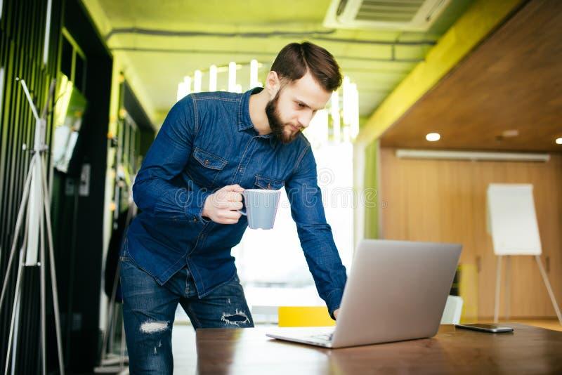 Hübscher männlicher Unternehmer, der an seinem Schreibtisch und an etwas auf dem Schirm seines Computers steht lizenzfreies stockbild