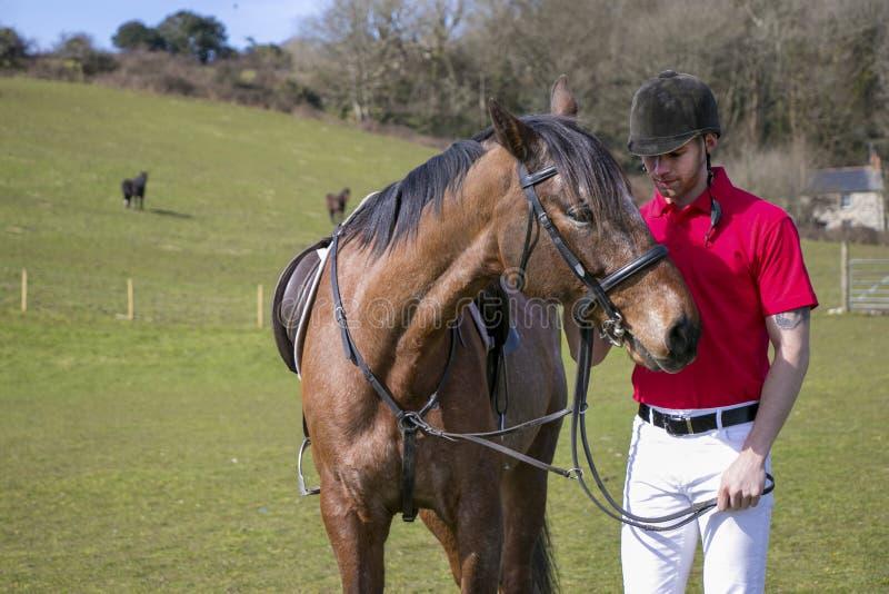 Hübscher männliches Pferdereiter, der nahe bei Pferd steht lizenzfreie stockfotos