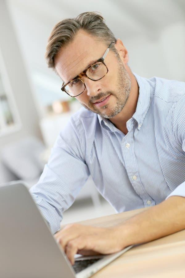 Hübscher Mann von mittlerem Alter, der an Laptop arbeitet stockbilder