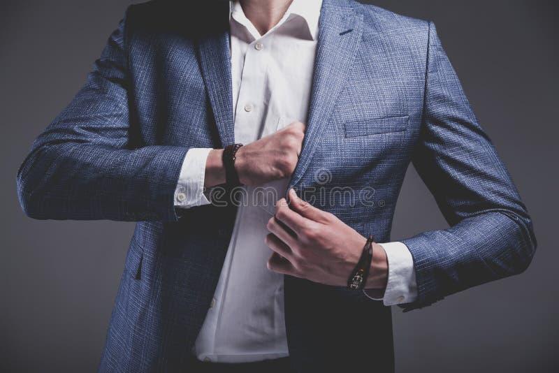 Hübscher Modegeschäftsmann kleidete in der eleganten blauen Klage auf grauem Hintergrund an stockfotos