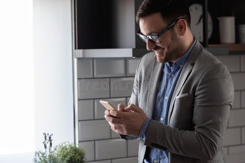 Hübscher moderner Geschäftsmann, der zuhause Smartphone verwendet stockbild