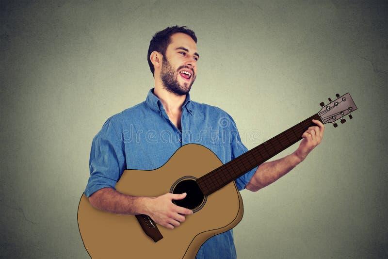 Hübscher Musiker, der die Gitarre singt ein Lied spielt stockbild