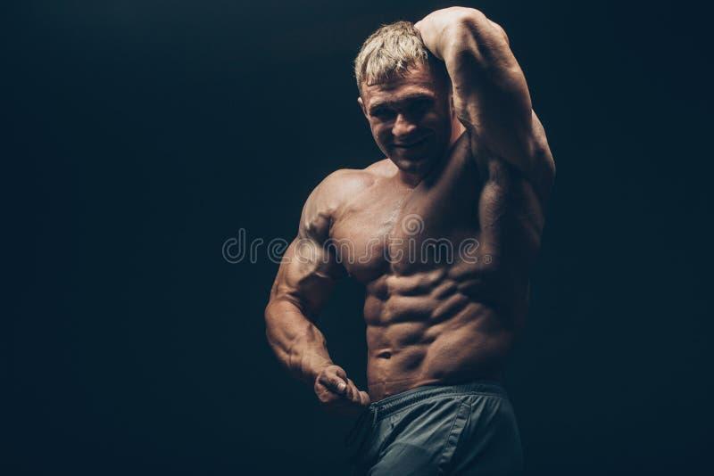 Hübscher muskulöser Bodybuilder, der über Schwarzem aufwirft lizenzfreies stockfoto