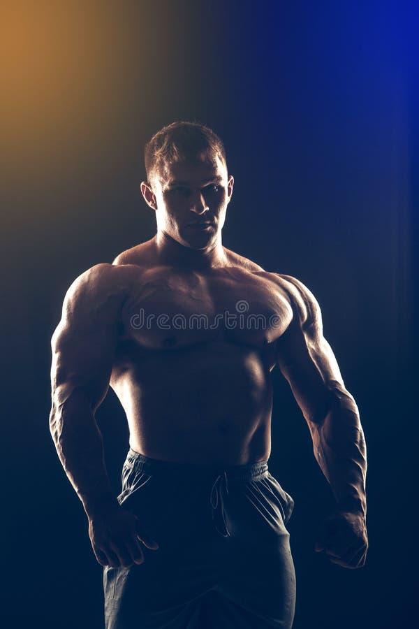 Hübscher muskulöser Bodybuilder, der über Schwarzem aufwirft stockbild