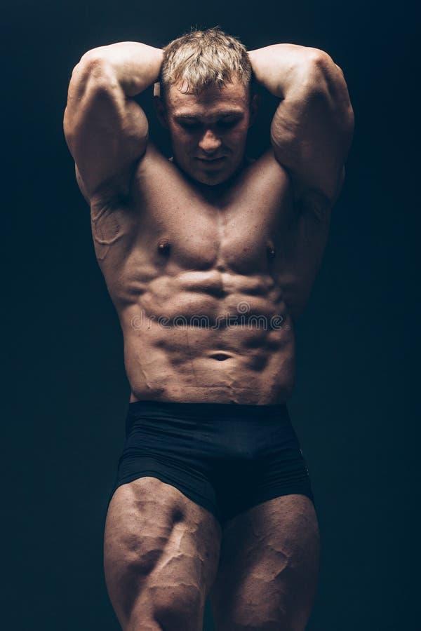 Hübscher muskulöser Bodybuilder, der über Schwarzem aufwirft stockbilder