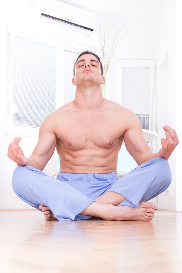 Hübscher muskulöser halb nackter Yoga tuender und meditierender Mann lizenzfreie stockfotografie