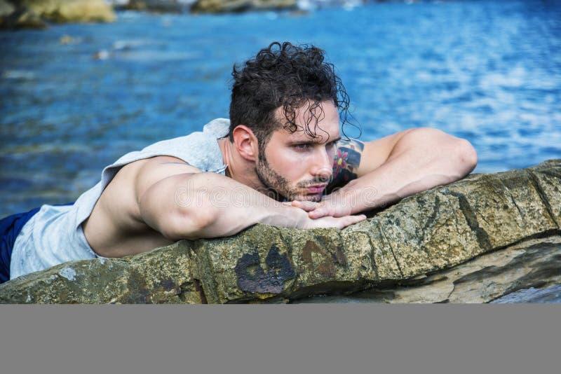 Hübscher muskulöser Mann auf dem Strand, der auf Felsen sitzt stockbilder