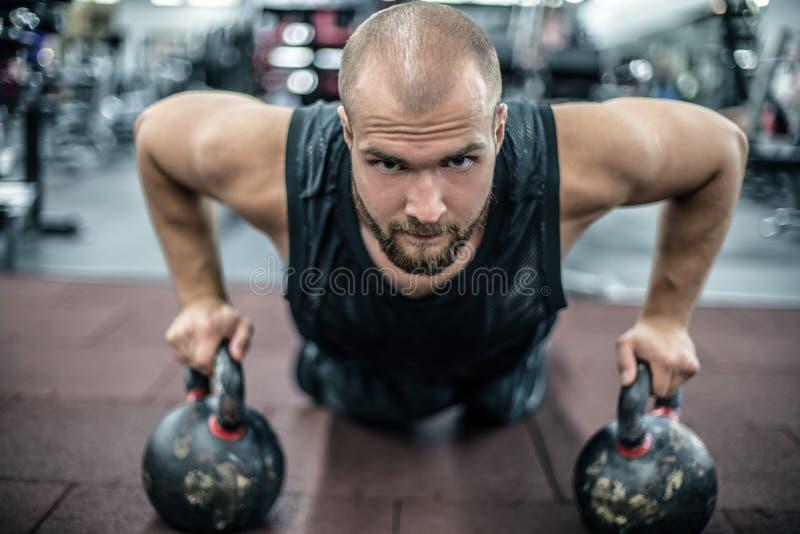 Hübscher muskulöser Mann, den das Handeln drückt, ups auf kettleball in crossfit Turnhalle stockfotos
