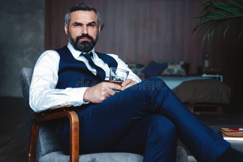 Hübscher nachdenklicher Mann berührt seinen Bart, schaut weg und denkt beim im Lehnsessel zuhause sitzen lizenzfreies stockfoto