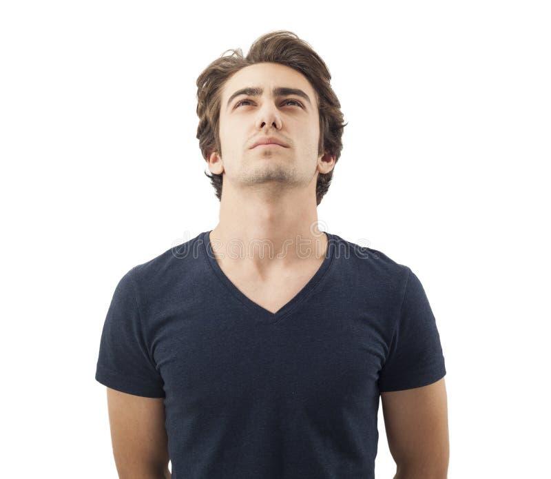 Hübscher nachdenklicher Mann, der oben auf Weiß schaut stockfoto