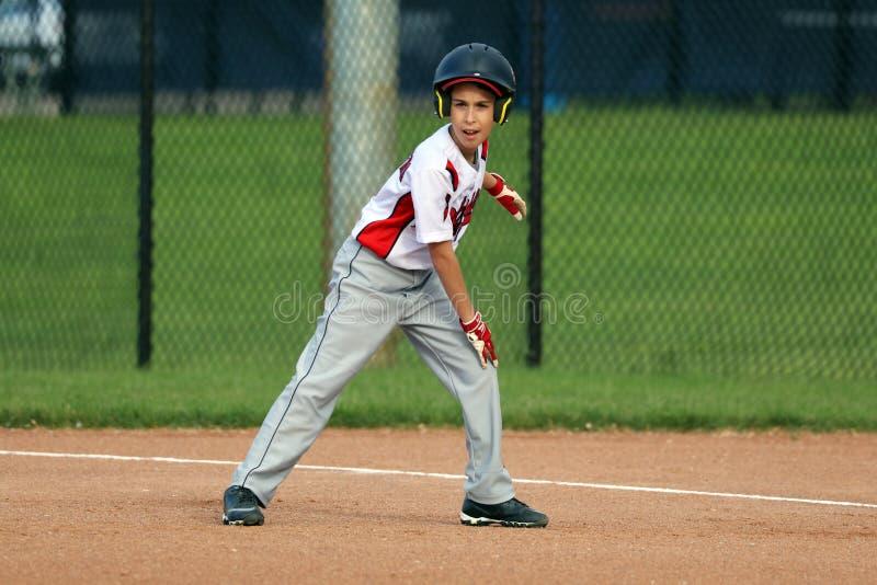 Hübscher netter Junge, der den Baseball wartet und schützt die Basis spielt stockbild