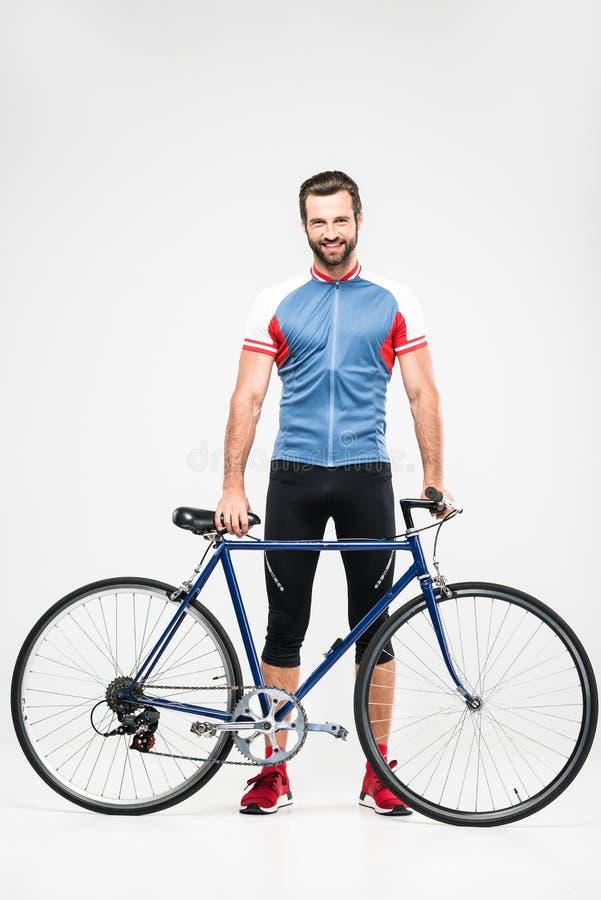 hübscher netter Radfahrer in der Sportkleidung, die mit Fahrrad aufwirft, lizenzfreies stockbild
