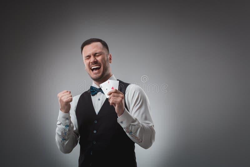 Hübscher Pokerspieler mit zwei Assen in seinen Händen stockfotografie