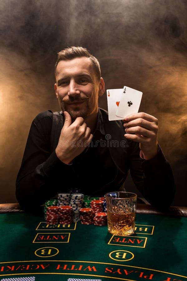 Hübscher Pokerspieler mit zwei Assen in seinen Händen und in Chips, die voll am Pokertisch in einer Dunkelkammer des Zigarettenra stockbilder