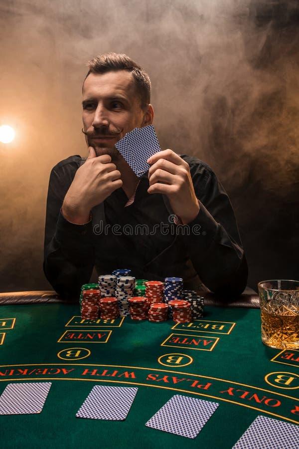Hübscher Pokerspieler mit zwei Assen in seinen Händen und in Chips, die voll am Pokertisch in einer Dunkelkammer des Zigarettenra lizenzfreies stockfoto