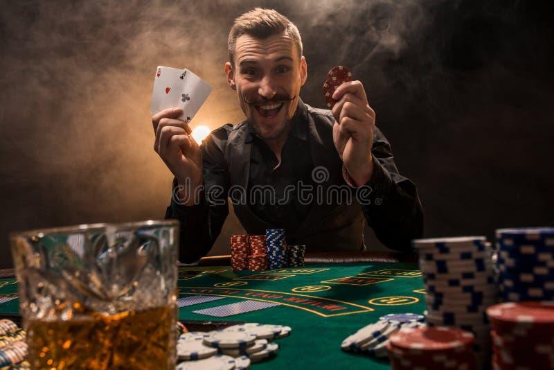 Hübscher Pokerspieler mit zwei Assen in seinen Händen und in Chips, die voll am Pokertisch in einer Dunkelkammer des Zigarettenra lizenzfreies stockbild