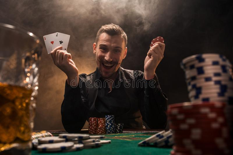 Hübscher Pokerspieler mit zwei Assen in seinen Händen und in Chips, die voll am Pokertisch in einer Dunkelkammer des Zigarettenra lizenzfreie stockbilder