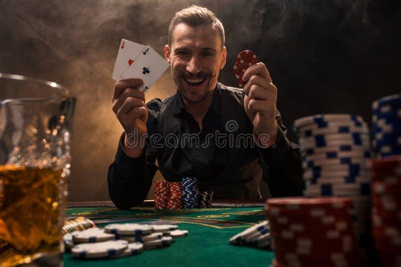 Hübscher Pokerspieler mit zwei Assen in seinen Händen und in Chips, die voll am Pokertisch in einer Dunkelkammer des Zigarettenra lizenzfreie stockfotografie