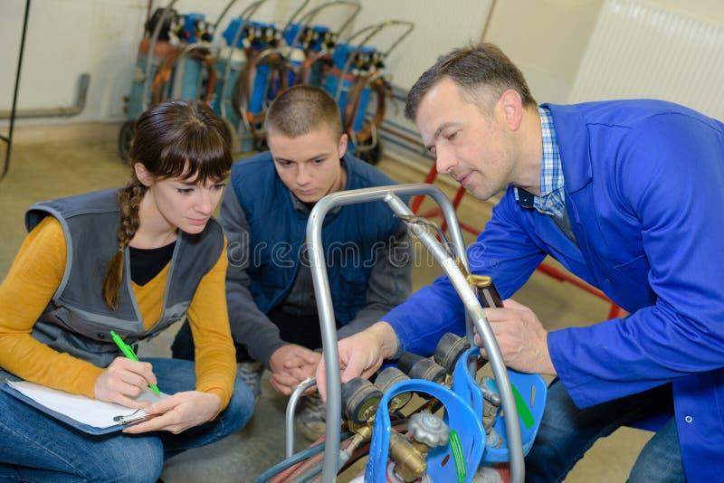 Hübscher Praktikant nimmt Notizen auf professionellem Metallurgiekurs stockfotos