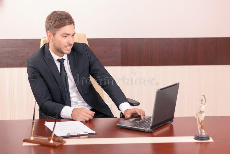 Hübscher Rechtsanwalt, der an seinem Laptop arbeitet stockbilder