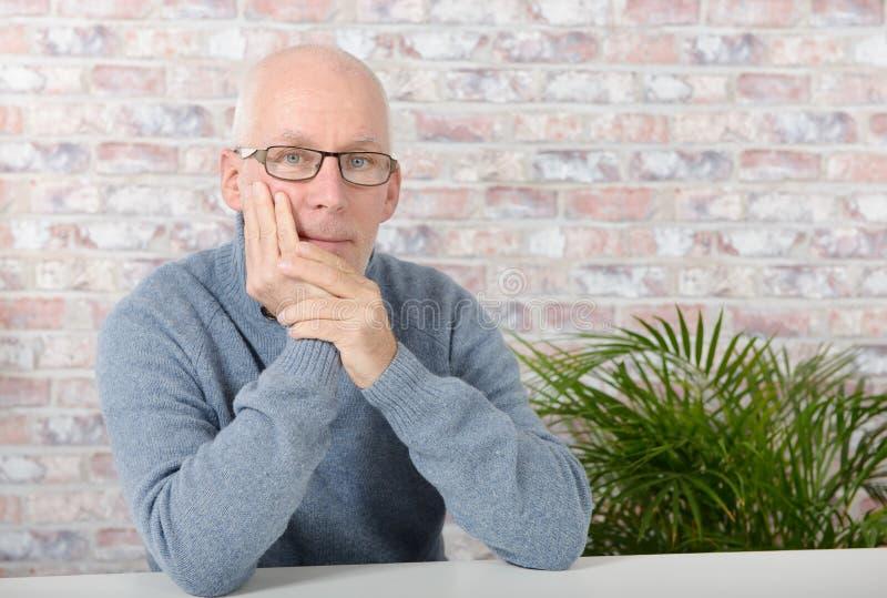 Hübscher reifer Mann mit blauem Pullover lizenzfreie stockfotografie