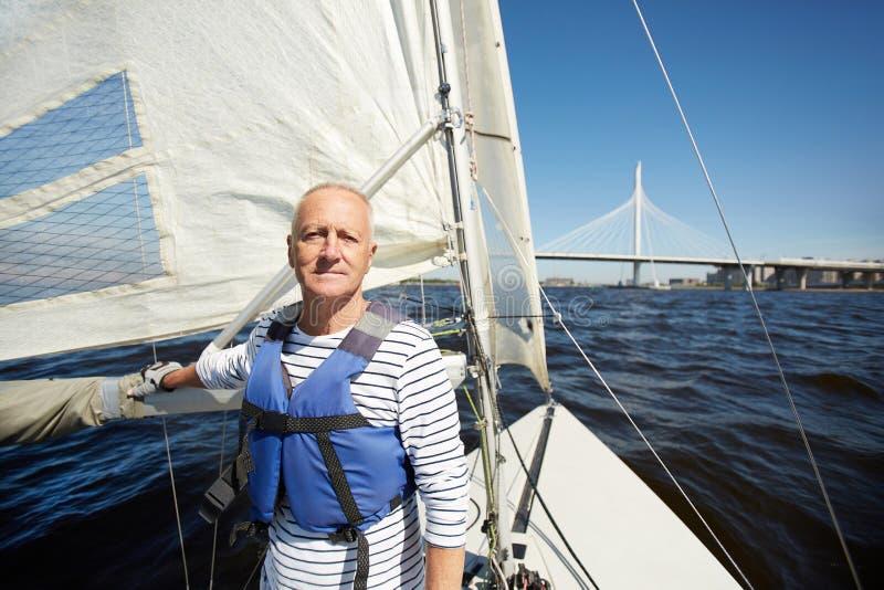 Hübscher reifer Yachtinhaber im Meer lizenzfreie stockfotos