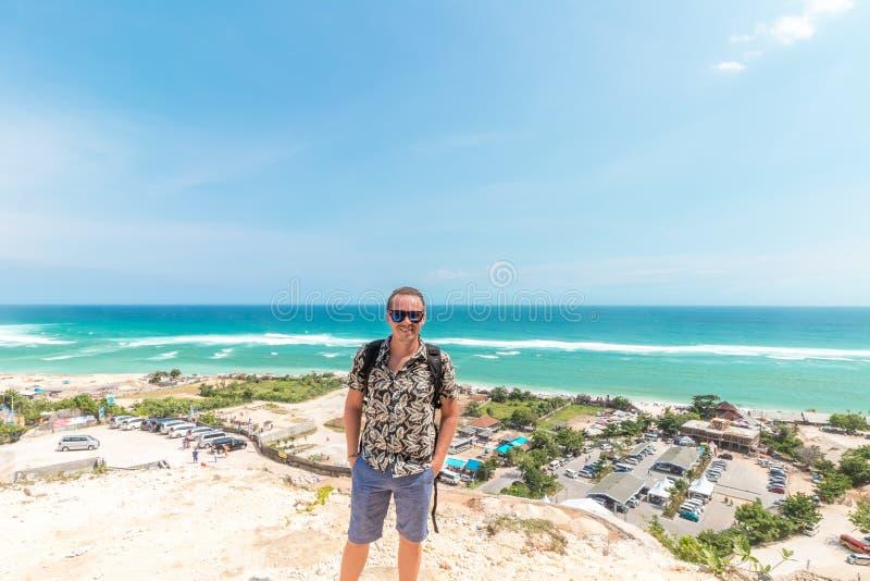 Hübscher Reisendmannaufenthalt durch blauen Ozeanhintergrund - glücklicher Kerl, der am Seestandpunkt sich entspannt - Konzept de lizenzfreie stockbilder