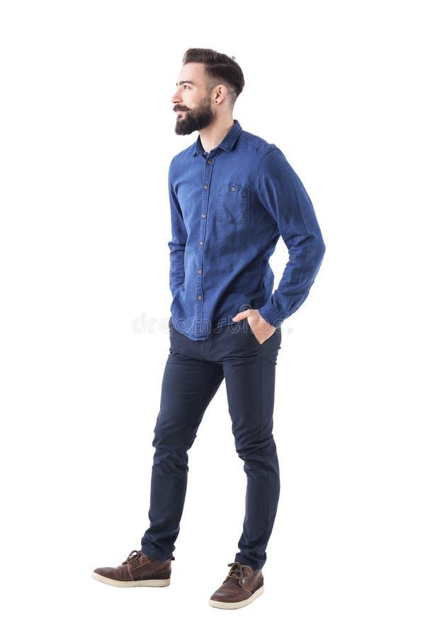 Hübscher reizend bärtiger zufälliger Mann des Geschäfts mit den Händen in den Taschen, die weg schauen und im Lächeln stockfotografie