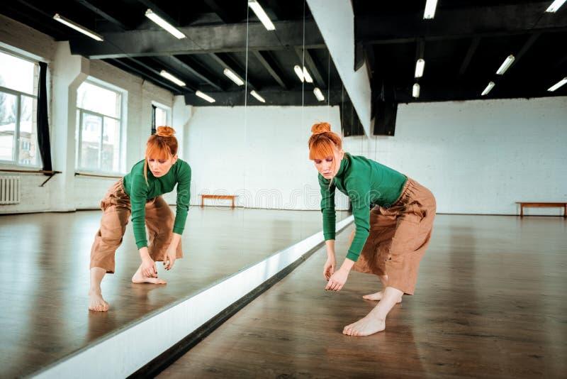 Hübscher rothaariger Berufstänzer in einem grünen Rollkragen, der konzentriert schaut stockfotos
