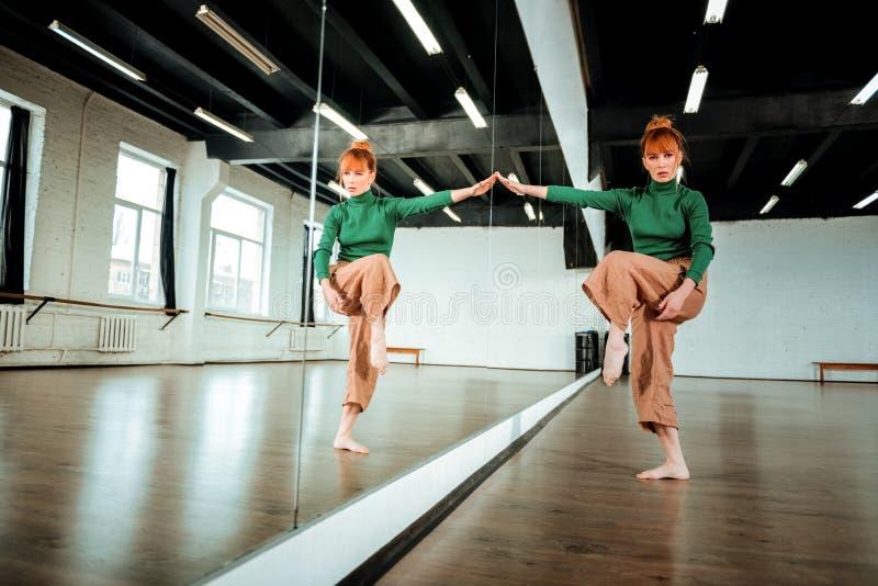 Hübscher rothaariger Berufstänzer in einem grünen Rollkragen, der rhythmische Gymnastik tut stockfotografie