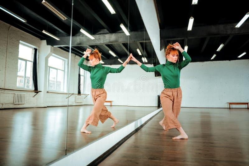 Hübscher rothaariger Berufstänzer in einer grünen Rollkragenstellung in einer tanzenden Position lizenzfreies stockfoto