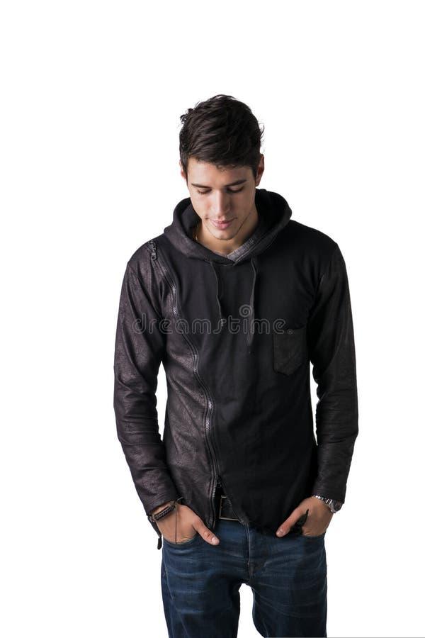 Hübscher schüchterner junger Mann in der schwarzen Hoodiestrickjackenstellung lizenzfreies stockbild