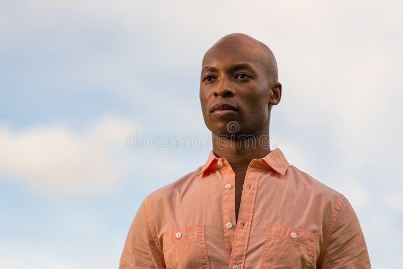Hübscher schwarzer Geschäftsmann des Porträts, der über der Kamera flüchtig blickt Hellblauer bewölkter Himmel im Hintergrund mit stockfotografie