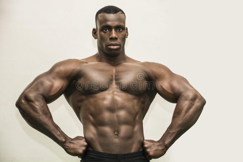 Hübscher schwarzer männlicher Bodybuilder, der im Studio aufwirft lizenzfreie stockfotografie