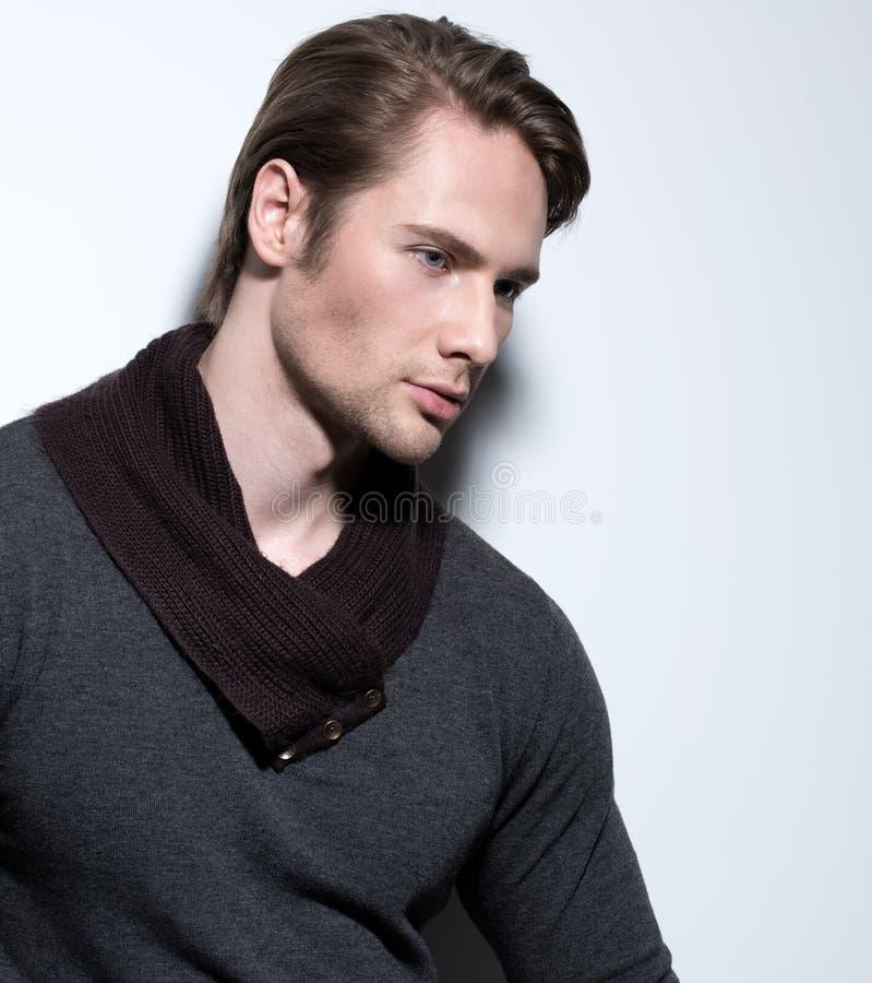 Hübscher sexy Mann im grauen Pullover. stockfotografie