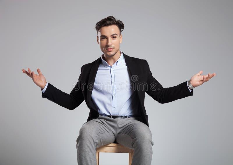 Hübscher Sitzgeschäftsmann, der ein freundliches Handzeichen macht stockfoto