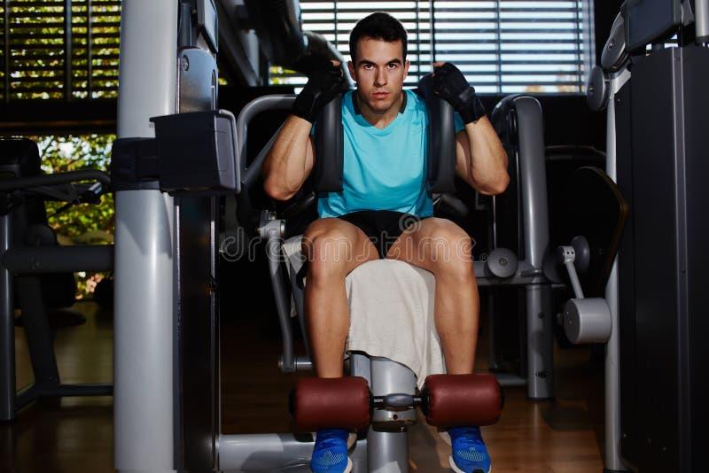 Hübscher Sitzmann, der mit den Bauchmuskeln ausarbeitet stockfoto