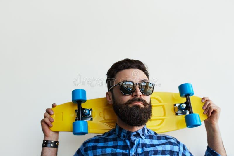 Hübscher Skateboardfahrer, ein Skateboard hinter seinem Kopf halten stockfotografie