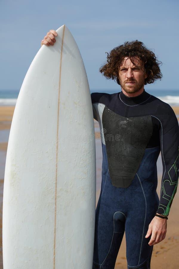 Hübscher sportiver Mann in einem Nierenfett für die surfende Aufstellung auf dem Strand am sonnigen Tag stockfotos