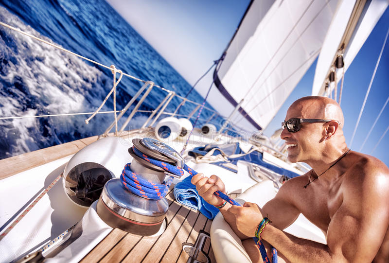 Hübscher starker Mann, der an Segelboot arbeitet lizenzfreie stockfotos