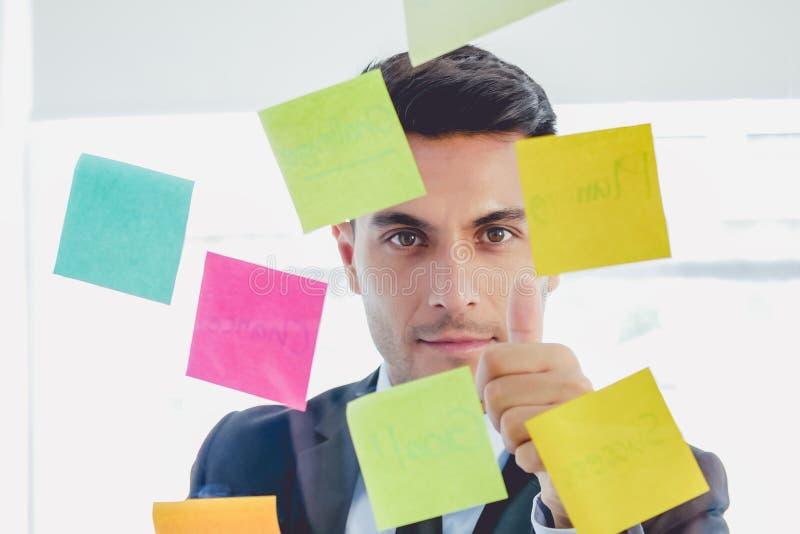 Hübscher Startgeschäftsmann, der gerade klebrige Anmerkungen und Daumen oben in den Glasständen im kreativen Büro schaut lizenzfreie stockbilder