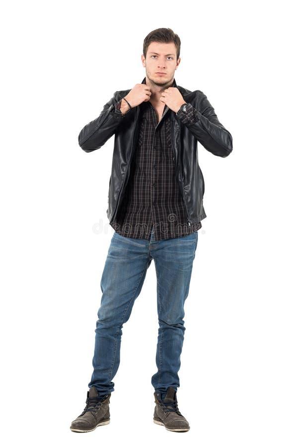 Hübscher Stellring des jungen Mannes der schwarzen Lederjacke Kamera betrachtend lizenzfreies stockbild