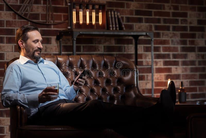 Hübscher stilvoller Geschäftsmann, der auf dem Tisch seine Beine setzt lizenzfreies stockbild
