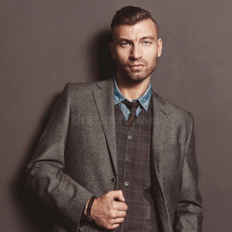 Hübscher stilvoller Mann des Mode-Modells in der Klage auf grauem Wandhintergrund Eleganter moderner schöner grober Mann stockbild