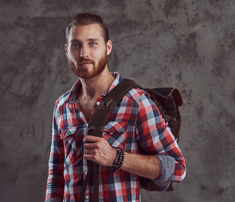 Hübscher stilvoller Rothaarigereisender in einem Flanellhemd mit einem Rucksack, werfend in einem Studio auf einem grauen Hinterg stockbilder