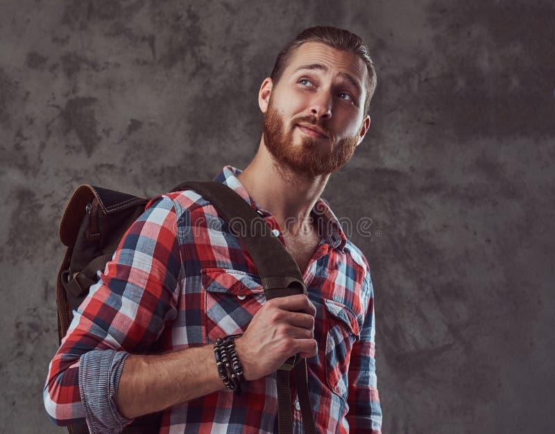 Hübscher stilvoller Rothaarigereisender in einem Flanellhemd mit einem Rucksack, werfend in einem Studio auf einem grauen Hinterg stockbild