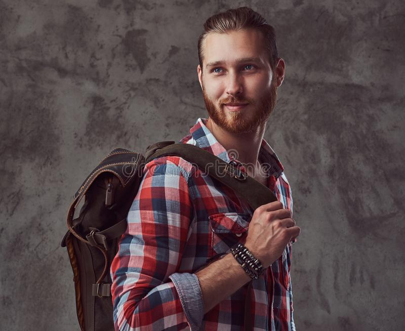 Hübscher stilvoller Rothaarigereisender in einem Flanellhemd mit einem Rucksack, werfend in einem Studio auf einem grauen Hinterg lizenzfreie stockbilder